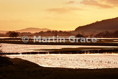 Flooded Lyth Valley with golden glow after sunset, Lake District National Park, England