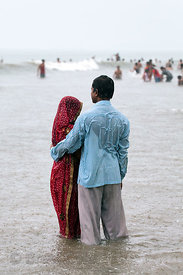 A couple stand poetically at the edge of the Arabian Sea in monsoon rains at Juhu Beach, Mumbai, India.