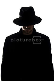 An image of a mystery man in a black coat and Fedora hat.