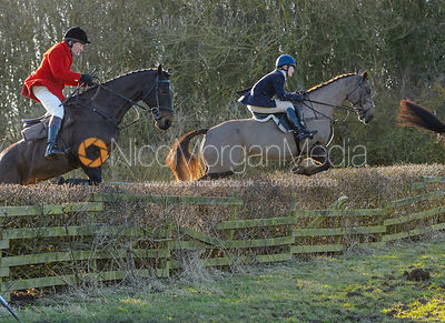 Richard Hunnisett, Rachel Finnegan jumping a hedge at Town Park Farm - The Cottesmore at Town Park Farm
