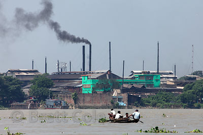 A ferry on the Hooghly River in Kolkata, India, with a factory in the background belching black smoke from a stack. Kolkata h...