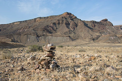 A cairn of rocks stands in a dry dead grasses with baren rocky mountains in the background.