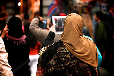 Woman of a Middle Eastern appearance using  iPad Camera