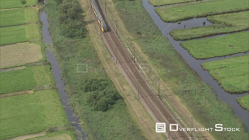 Looking down at a train on the tracks through a rural landscape in The Netherlands