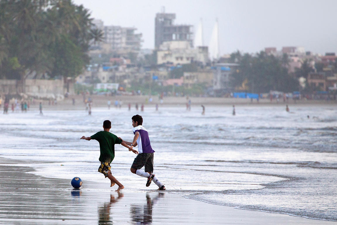 Boys playing soccer on Juhu Beach, Mumbai, India.