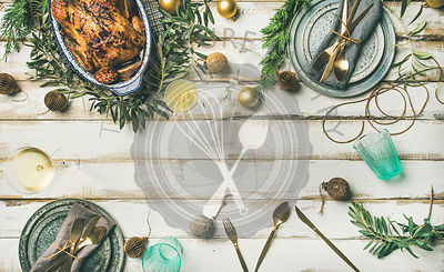 Flat-lay of roast chicken, plates, silverware, glass and toy holiday decoration over rustic white wooden background