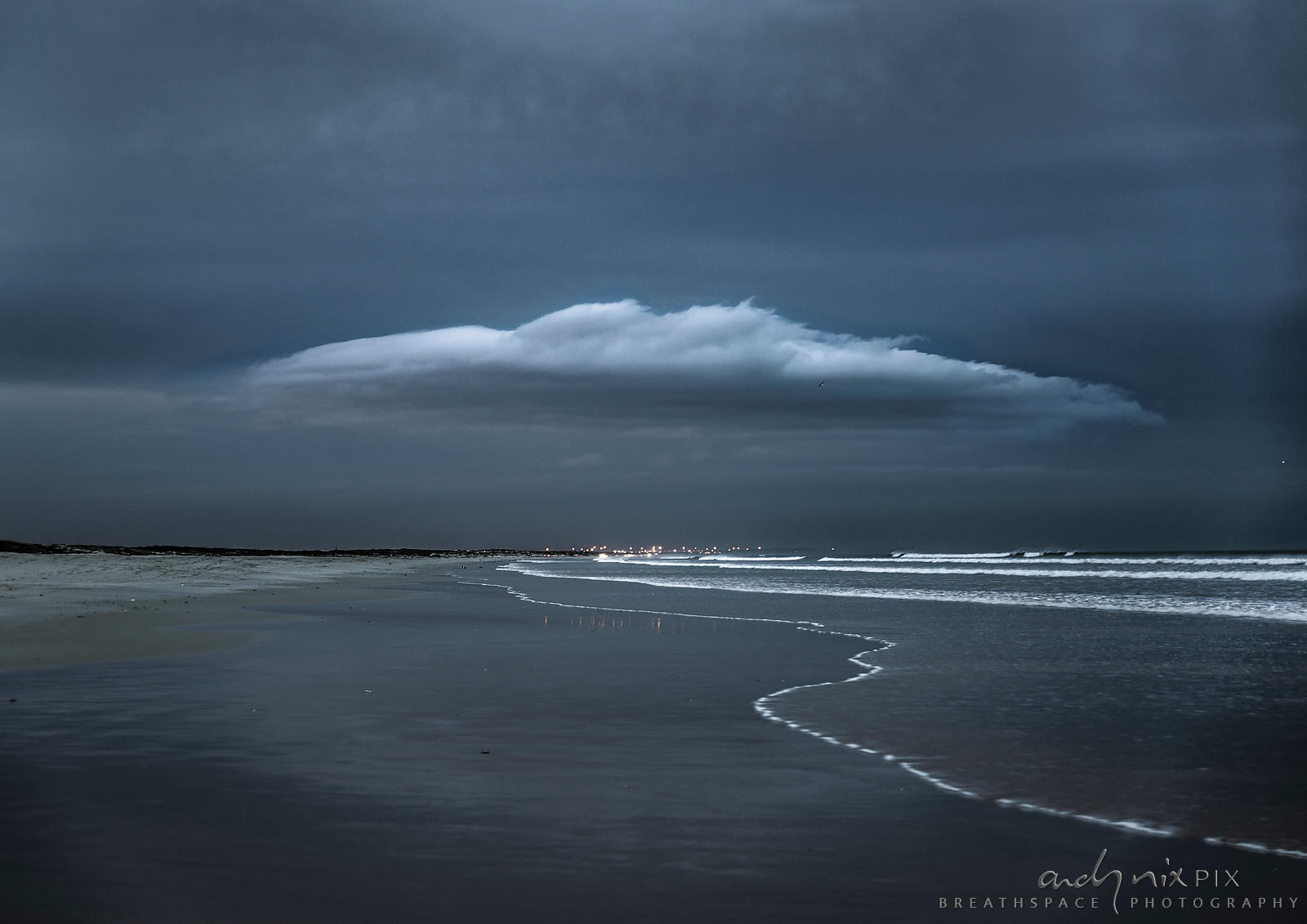 Grey UFO-shaped cloud over a beach at night, lights in the distance.