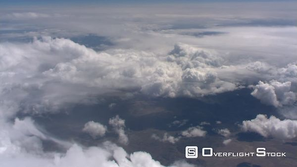 Flight over billowing cloud masses with arid terrain below