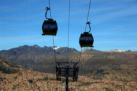 Yellow Line cable car gondolas above La Paz suburbs, Cordillera Real mountains in background, Bolivia