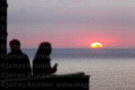 People watching sun sinking below horizon from Larcomar, Miraflores, Lima, Peru