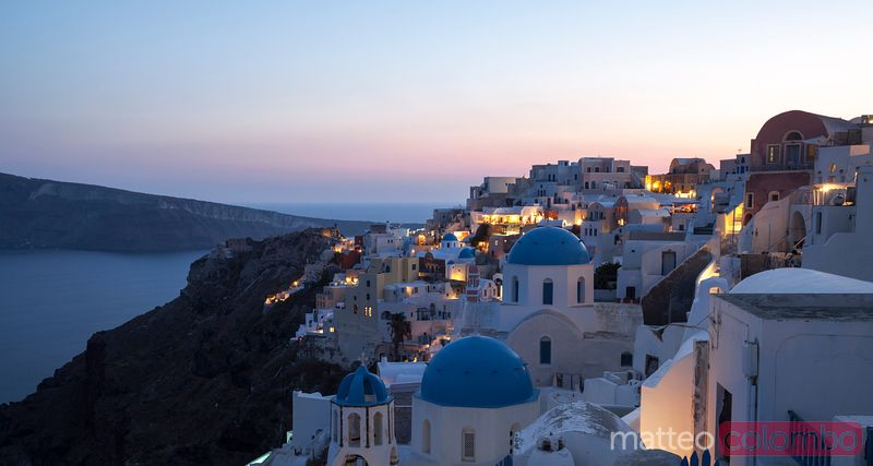 Village of Oia with blue domed churches at sunset