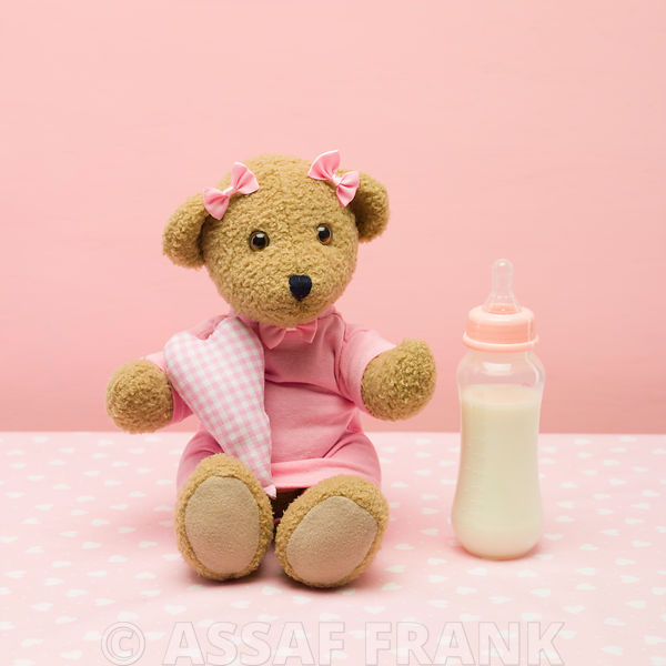 Baby teddy bear with a little heart and milk bottle
