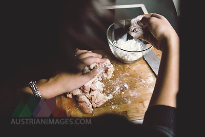 Woman coating chicken with corn starch