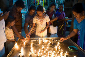 India - Swamimalai - Devotees light oil lamps in the Murugan temple