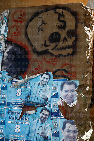 Old political campaign posters and skull with dollar sign graffiti on wall, La Paz, Bolivia