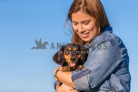 smiling woman looking down at dog in her arms