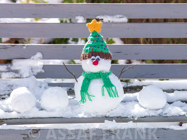 Snowman on bench covered with snow outdoors
