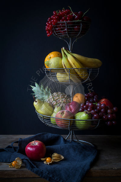 Fresh fruits in metal étagère before dark background