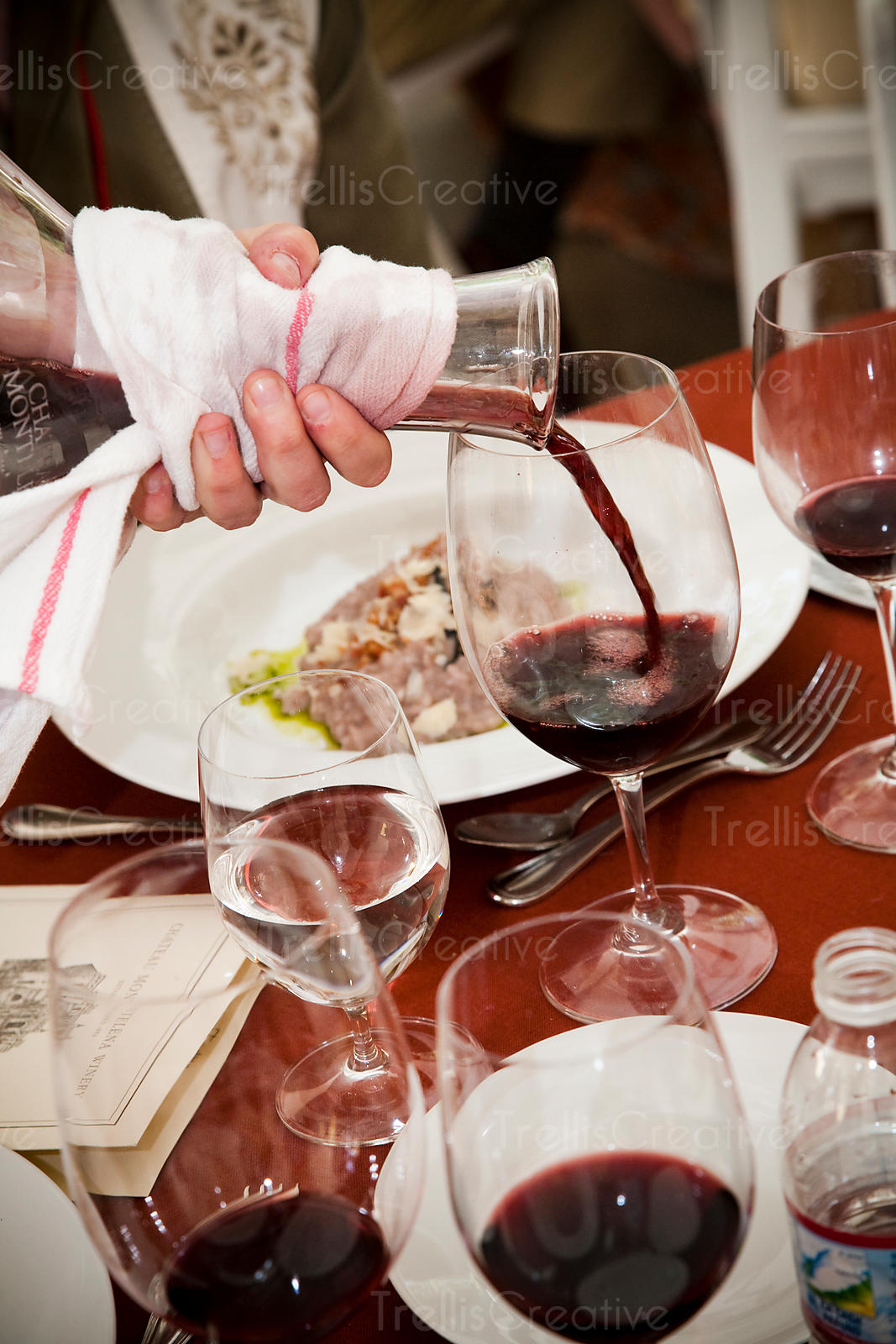 Server pouring red wine from a crystal decanter