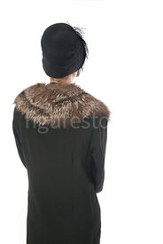 A vintage 1920's woman in a long coat, hat and fur – shot from eye level.