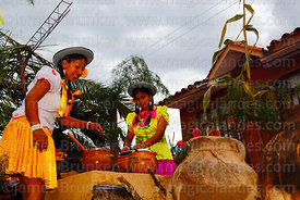 Girls wearing traditional dress preparing chicha on the back of a truck during Carnival parades, San Lorenzo, Tarija Departme...