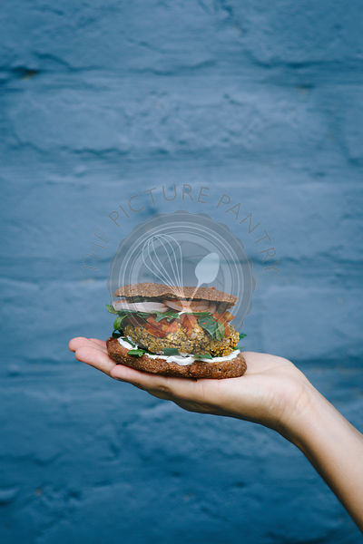 Vegan burgers with tomato salsa on the girl's hand