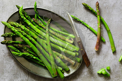 Trimmed organic asparagus spears on a plate.
