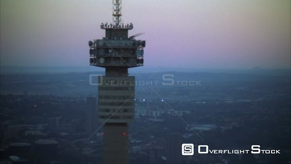 Aerial of the Hillbrow Tower moving further away to reveal Johannesburg Central Business District at sunset/sunrise. Johannes...
