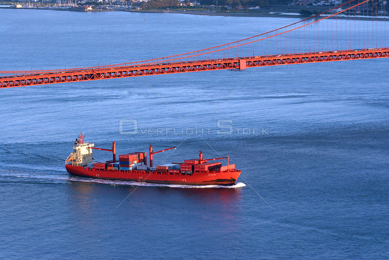 Red Cargo ship passing under the Golden Gate Bridge, San Francisco Bay, California