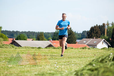 Mature man running on meadow