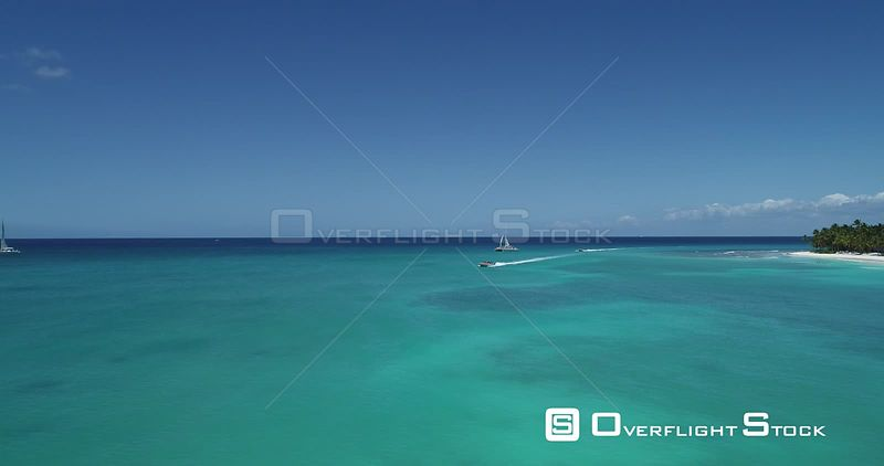 Caribbean sea with beach and speed boat. Flight backward over the sea . Saona Island, Dominican Republic